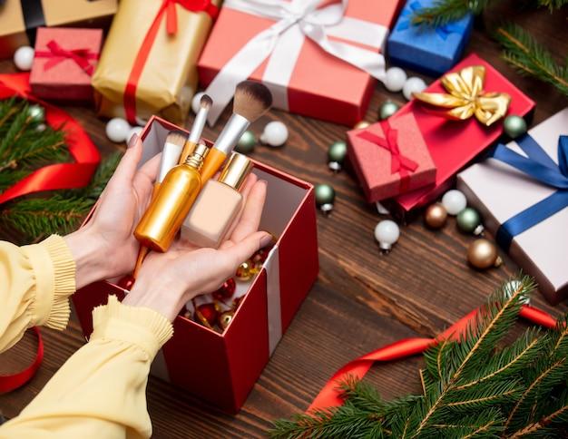 La mano femminile tiene i cosmetici vicino ai regali di natale