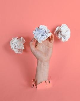 La mano femminile tiene le sfere di carta sgualcite attraverso carta gialla strappata. idea minimalista il concetto di business
