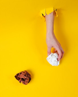 La mano femminile tiene le palle di carta sgualcite attraverso la carta gialla lacerata. concetto di business idea minimalista