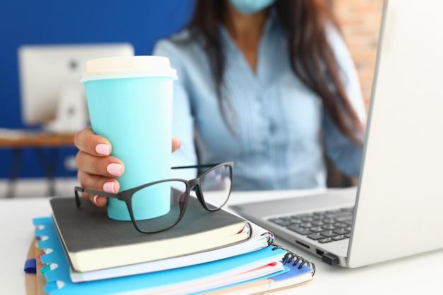 La mano femminile tiene la tazza di caffè sul posto di lavoro.