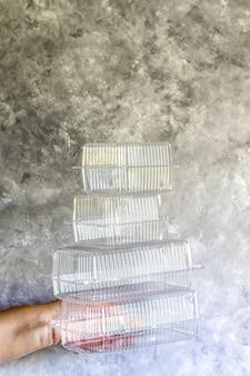 La mano femminile tiene stoviglie usa e getta per la consegna a domicilio. su un tavolo grigio.