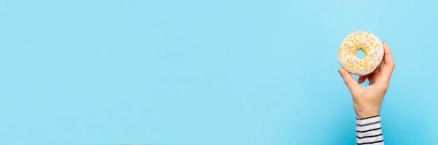 La mano femminile tiene una ciambella su un blu. negozio di pasticceria di concetto, pasticceria, caffetteria