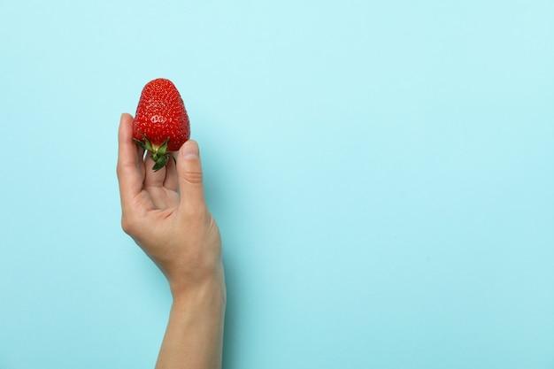 La mano femminile tiene la fragola fresca sulla superficie blu