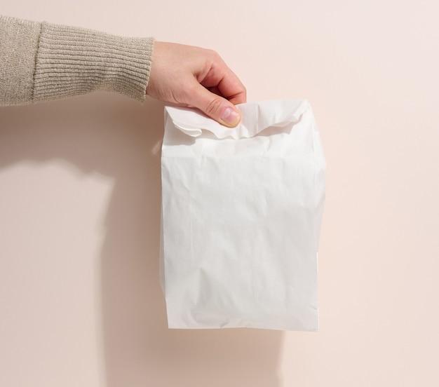 La mano femminile tiene un sacco di carta pieno su uno sfondo beige. rifiuto di imballaggi in plastica, consegna di cibo