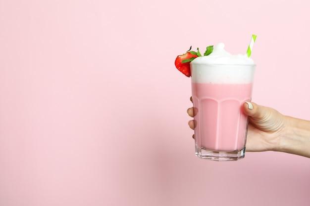 La mano femminile tiene un bicchiere di frullato alla fragola su sfondo rosa