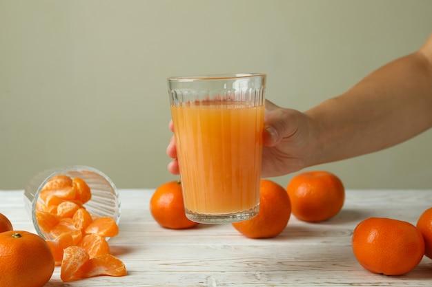 La mano femminile tiene il bicchiere con succo di mandarino, primo piano