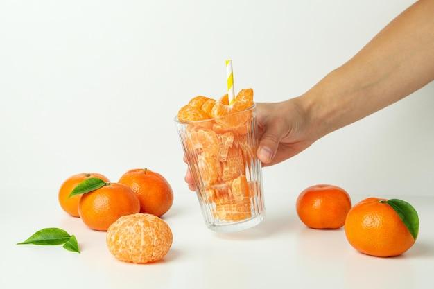 La mano femminile tiene il vetro con le fette del mandarino su fondo bianco