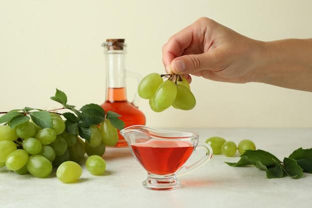 La mano femminile tiene l'uva sopra la salsiera con aceto