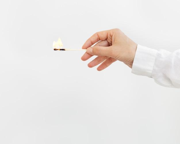 La mano femminile tiene il fiammifero acceso su sfondo chiaro. fiammifero in legno con fuoco.
