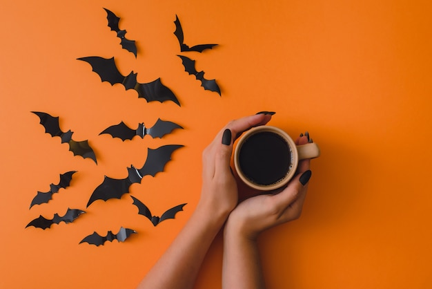 Una mano femminile tiene una tazza con caffè su uno sfondo arancione con pipistrelli decorativi. concetto tradizionale, di festa e di festa. halloween. vista dall'alto piatto