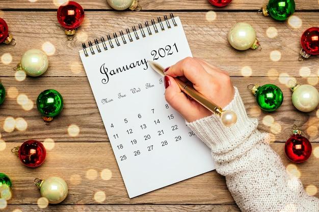Mano femminile tiene la penna, calendario aperto gennaio 2021, decorazioni natalizie sulla tavola di legno