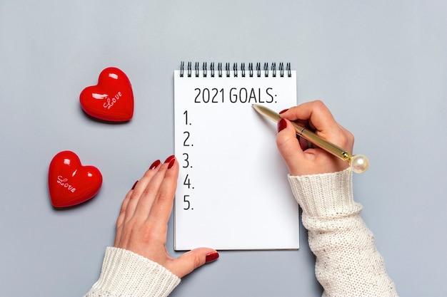 La mano femminile tiene la penna e scrive gli obiettivi del nuovo anno 2021 sul blocco note bianco, due cuori rossi su gray