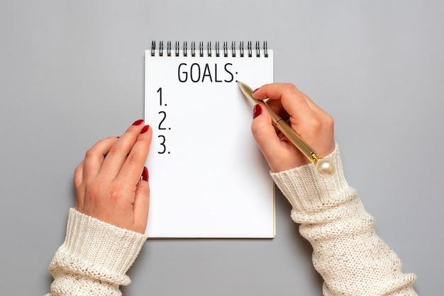 La mano femminile tiene la penna e scrive gli obiettivi del nuovo anno del testo 2021 sul blocco note bianco su gray