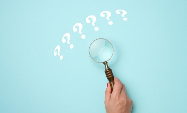 La mano femminile tiene una lente d'ingrandimento di plastica e dei punti interrogativi su uno sfondo blu. il concetto di trovare una risposta a domande, verità e incertezza.