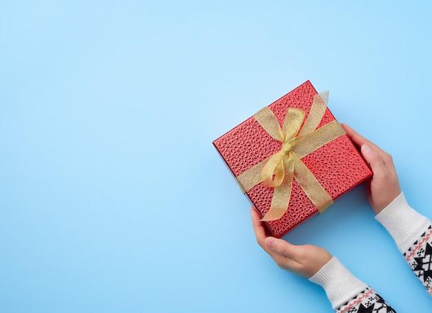 La mano femminile tiene una scatola rossa legata con un nastro dorato, il concetto delle congratulazioni e i regali