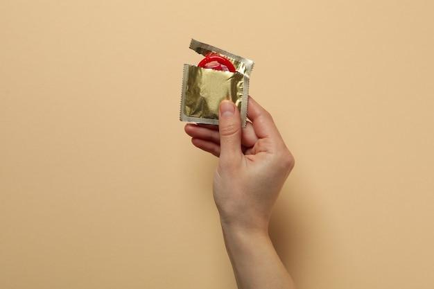 La mano femminile tiene il preservativo rosso sulla superficie beige