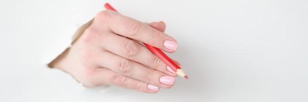 La mano femminile tiene la matita rossa nel foro di carta bianca