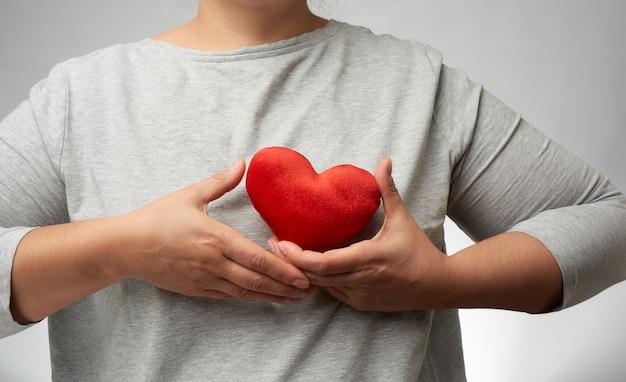 La mano femminile tiene un cuore rosso della tessile vicino al petto