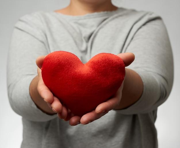 La mano femminile tiene un cuore rosso della tessile
