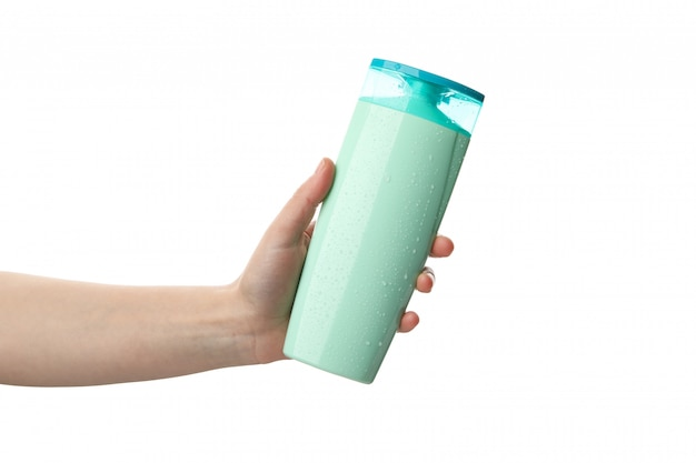La mano femminile tiene la bottiglia dello shampoo, isolata su fondo bianco