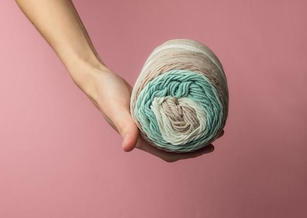 La mano femminile tiene una matassa di fili di lana su sfondo rosa pastello per studio.
