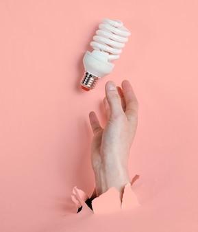 La mano femminile tiene la lampadina a spirale attraverso carta rosa strappata. concetto di moda creativa minimalista