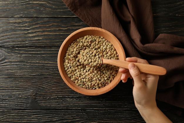 La mano femminile tiene un cucchiaio con i legumi sopra una ciotola di legumi sulla tavola di legno