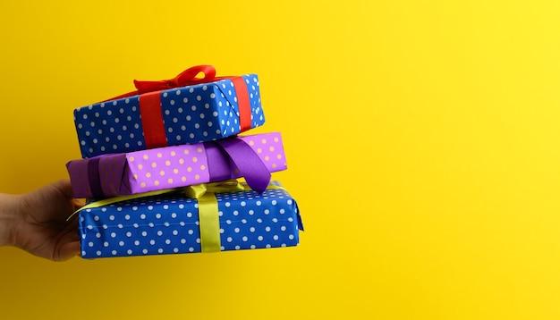 La mano femminile tiene una pila di scatole regalo legate con un nastro di seta su uno sfondo giallo, copia spazio