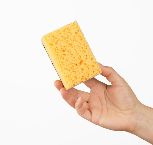 La mano femminile tiene una spugna gialla della cucina per lavare i piatti, parte del corpo su una priorità bassa bianca