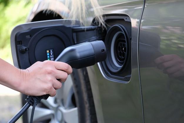 La mano femminile inserisce la spina per caricare il primo piano dell'auto elettrica
