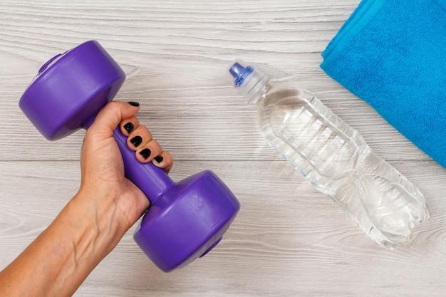 La mano femminile tiene un manubrio in camera o in palestra con una bottiglia d'acqua e un asciugamano sullo sfondo. strumenti per il fitness. vista dall'alto
