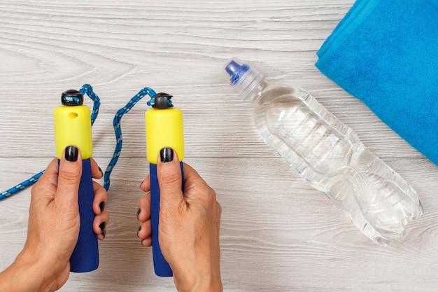 La mano femminile tiene la corda per saltare in camera o in palestra con una bottiglia d'acqua e un asciugamano sullo sfondo.