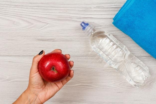 La mano femminile tiene in mano una mela rossa in camera o in palestra con una bottiglia d'acqua e un asciugamano sullo sfondo.