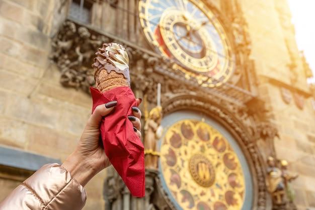La mano femminile sta tenendo il trdelnik ceco tradizionale del biscotto su fondo dell'orologio astronomico nella città di praga.