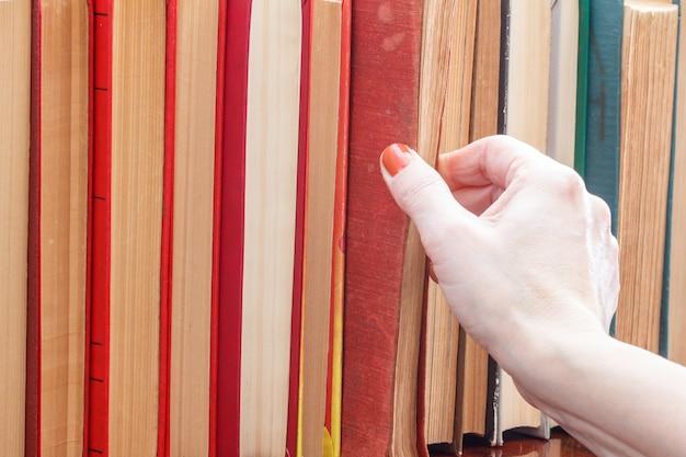 La mano femminile sta prendendo un vecchio libro dallo scaffale. molti libri con copertina rigida su scaffale in legno. concetto di educazione