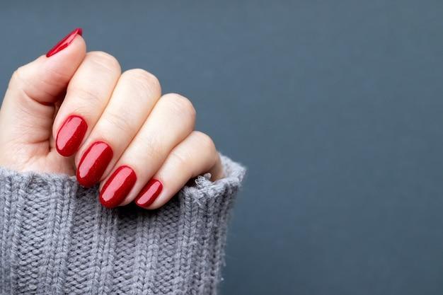 Mano femminile in maglione lavorato a maglia con bella manicure - unghie luccicanti rosse su sfondo grigio con spazio di copia. messa a fuoco selettiva. vista del primo piano