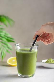 Mano femminile mescolando acqua con polvere superfood verde