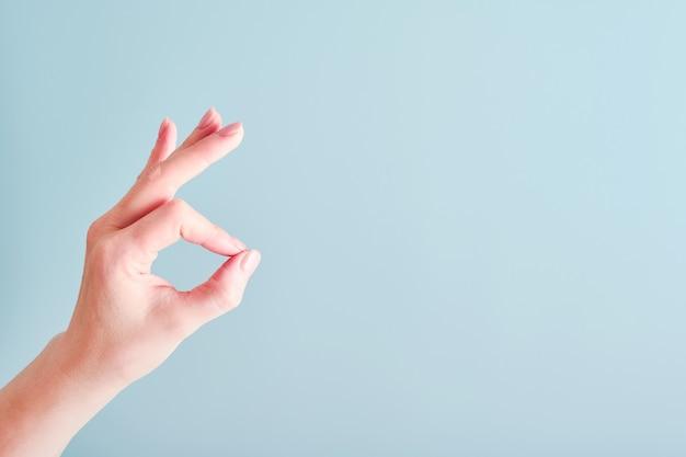 Segno giusto della mano femminile su fondo azzurro. messa a fuoco selettiva. modello. copia spazio.