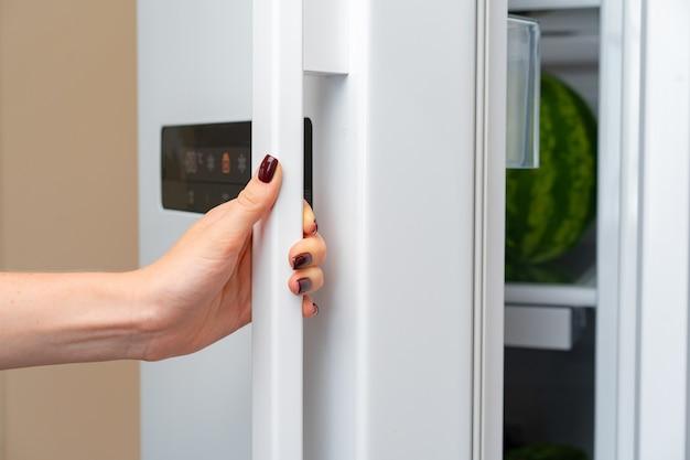 La mano femminile apre la porta di un frigorifero