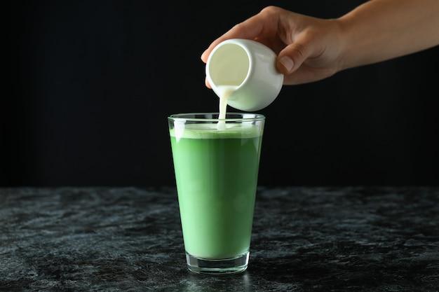Mano femminile che versa il latte in un bicchiere di latte matcha su sfondo nero