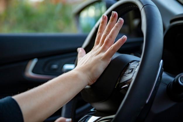 La mano femminile preme il clacson sul volante di un'auto moderna. senza volto