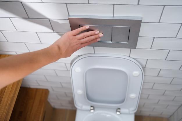 La mano femminile preme il primo piano del bottone dello sciacquone della toilette
