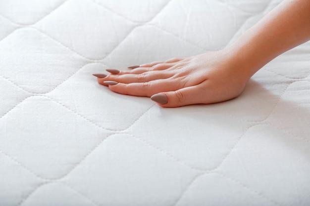 Mano femminile premendo il materasso di prova per verificare la morbidezza. materasso comodo di scelta per dormire in negozio. controllo qualità durezza dei materiali del materasso schiuma ortopedica. donna che sceglie nuovo materasso.