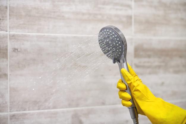 Mano femminile in guanto di gomma giallo protettivo che tiene la testa della doccia con versando acqua nel bagno domestico, copia spazio, sfocatura di movimento
