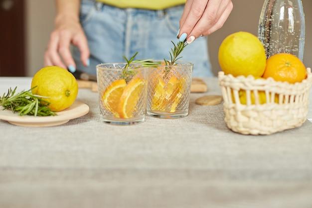 La mano femminile mette il rosmarino nei bicchieri, la donna che prepara, prepara la limonata fresca agli agrumi e al rosmarino in vetro su un tavolo bianco a casa, bevanda estiva, acqua salutare disintossicante.
