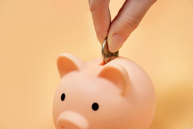 Una mano femminile mette una moneta in un primo piano del porcellino salvadanaio. concetto di accumulo di finanze.