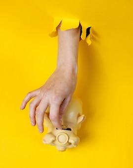 La mano femminile mette la moneta nel salvadanaio attraverso il foro di carta gialla strappata. concept creativo minimalista