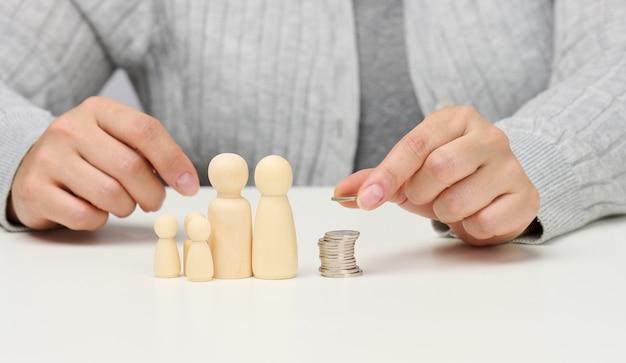 La mano femminile mette le monete in una pila e le figurine in legno di una famiglia su un tavolo bianco. economia e concetto di investimento, pianificazione del budget. ricevere sussidi dallo stato, tasse