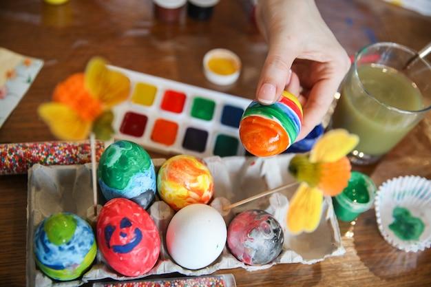 La mano femminile mette l'uovo di pasqua decorato con il resto delle uova nel supporto di lavorazione sul tavolo