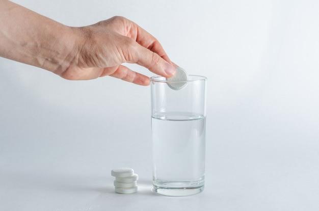 La mano femminile mette una compressa solubile effervescente in un bicchiere d'acqua